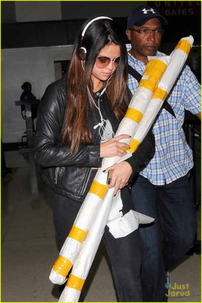 Selena Gomez has her hands full with some large rolled items as she arrives at LAX in Los Angeles